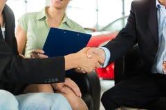 Händedruck am Auto-Vertragshändler mit Automobil Lizenzfreie Stockfotos