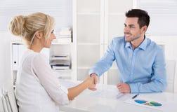 Händedruck: Berater sagt zu seinem weiblichen Kunden Guten Tag Lizenzfreie Stockfotos