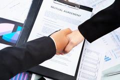 Händedruck btween Geschäftsfrau über Vereinbarung Stockfotos