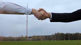 Händedruck gegen einen Hintergrund eines Telefonturms, Nahaufnahme stock footage