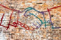 Händedruck gezeichnet auf eine Backsteinmauer - Konzeptbild stockfotografie