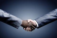 Händedruck - Hand, die ein Schwarzes anhält Lizenzfreie Stockfotos