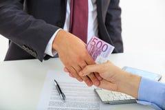 Händedruck mit Geld Stockfoto
