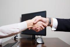 Händedruck von zwei gleichen Mitarbeitern über dem Schreibtisch Lizenzfreie Stockbilder
