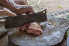 Händer är den högg av grisköttslaktaren Arkivfoto