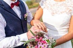 Händer ansar och bruden med vigselringar och blommar symbol för bukettberömförälskelse Royaltyfria Foton