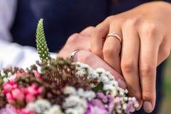 Händer ansar och bruden med vigselringar och blommar symbol för bukettberömförälskelse Arkivfoton