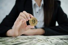 Händer av affärskvinnor som rymmer Bitcoin och pengardollaren, traver på royaltyfri foto