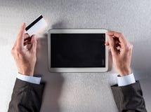 Händer av affärsmannen som ska köpas direktanslutet från hans digitala minnestavla Arkivbild