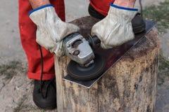 Händer av arbetaren i handskar behandlar ett ark av metall med en gri royaltyfria foton