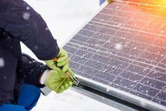 Händer av arbetaren som installerar solpaneler i snöig väder Närbild Arkivfoton