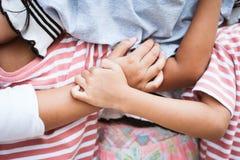 Händer av asiatiska barn som tillsammans rymmer och kramar Royaltyfri Bild
