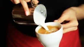 Händer av att hälla för kaffe för för baristadanandelatte eller cappuccino mjölkar danandelattekonst stock video