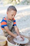 Händer av barn pillar, producerades på område av krukan Arkivbilder