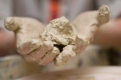 Händer av barnkeramikern som knådar lera fotografering för bildbyråer