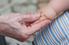 Händer av behandla som ett barn sonsonen och den gamla farmodern, det beträffande begreppet av familjen Arkivbild