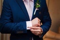 Händer av bröllopbrudgummen i en vit skjorta klär cufflinks Royaltyfri Foto