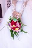 Händer av bruden i en vit klänning med en bukett av röda rosor Royaltyfri Bild