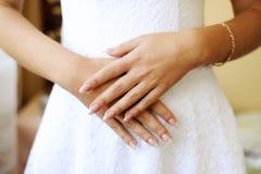 Händer av bruden korsas på en mage royaltyfri fotografi