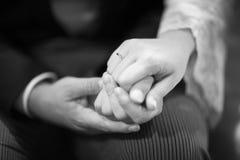 Händer av bruden och brudgummen i bröllopförbindelseceremoni Arkivbilder