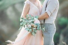 Händer av bruden och brudgummen med bröllopbuketten fotografering för bildbyråer