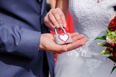 Händer av bruden och brudgummen med tappninglåset royaltyfria bilder