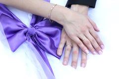 Händer av bruden och brudgummen och den lila pilbågen Royaltyfri Foto