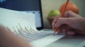 Händer av danandeanmärkningen för ung man med blyertspennan på utskrivavna analyserande grafer lager videofilmer