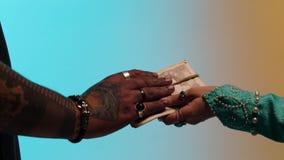 Händer av den östliga kvinnan med många cirklar som ger pengar, band med tvinnar upp till säljaremannen som isolerades på gult oc arkivfilmer