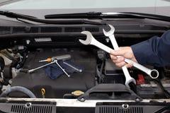 Händer av den auto mekanikern med skiftnyckeln. royaltyfria foton
