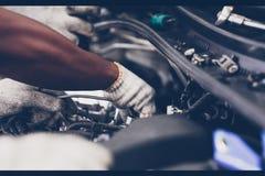 Händer av den auto mekanikern som reparerar bilen Selektivt fokusera fotografering för bildbyråer