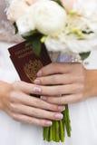 Händer av den bröllopdokument och buketten för brud hållande royaltyfria bilder