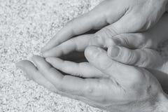 Händer av den flätade samman mannen och kvinnan Arkivbilder