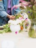 Händer av den gamla kvinnan som ordnar blommor Royaltyfri Bild