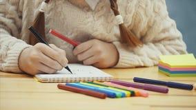 Händer av den gulliga skolbarnteckningen med röda och svarta markörer stock video