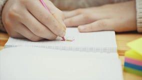 Händer av den idérika ungen som drar med den rosa blyertspennan i hennes anteckningsbok stock video