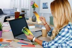 Händer av den kvinnliga formgivaren i regeringsställning som arbetar med färgprövkopior Arkivfoto
