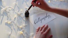 Händer av den kvinnliga konstnären skriver pennstilsorter med calligraphic bokstäver på tabellen med den flimrande girlanden i st lager videofilmer