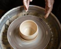 Händer av den ledar- keramikern och vasen av lera på keramiker`en s rullar Fotografering för Bildbyråer