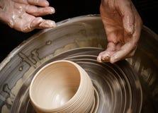 Händer av den ledar- keramikern och vasen av lera på keramiker`en s rullar Royaltyfria Foton