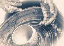 Händer av den ledar- keramikern och vasen av lera på keramiker`en s rullar Royaltyfria Bilder