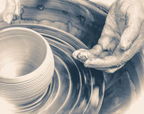Händer av den ledar- keramikern och vasen av lera på keramiker`en s rullar Arkivbild