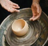 Händer av den ledar- keramikern och vasen av lera på keramiker`en s rullar Arkivfoton