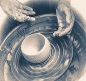 Händer av den ledar- keramikern och vasen av lera på keramiker`en s rullar Royaltyfri Fotografi