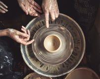 Händer av den ledar- keramikern och vasen av lera på keramiker`en s rullar Royaltyfri Foto