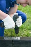 Händer av den ledar- vridningen skruven in i fundamentet med en skruvmejsel arkivfoton