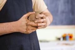 Händer av den manliga keramikerprofessionelln som gör en Clay Lump på arbetsbänken royaltyfri fotografi