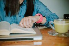 Händer av den unga kvinnan som ser klockan Royaltyfri Foto
