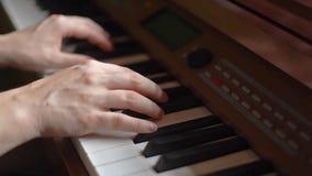 Händer av den unga kvinnan som spelar pianot lager videofilmer