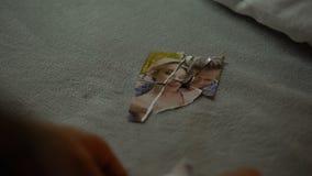 Händer av den unga mannen som försöker att sätta tillsammans delar av det sönderrivna fotoet med flickvännen lager videofilmer